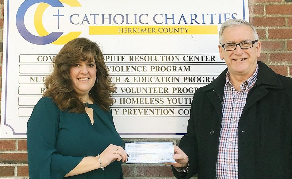 Tom Curnow delivers check to Catholic Charities